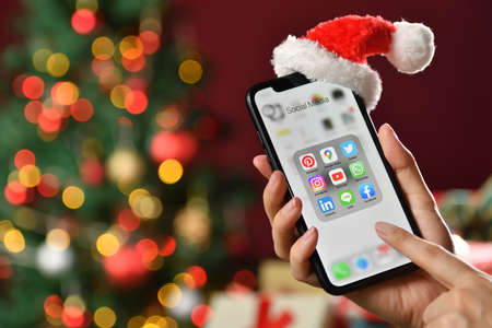 BANGKOK, THAILAND - OCTOBER 12,2020: Female holding smartphone with icons of social media on the screen on Christmas background