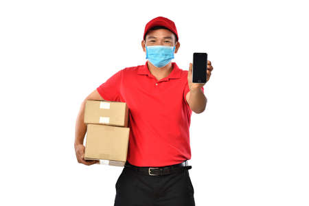 Happy young Asian delivery man in red uniform, medical face mask, protective gloves carry cardboard box showing mobile phone isolated on white background. Delivery guy give parcel shipment. Safe delivery