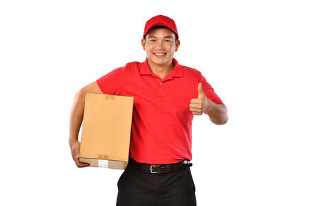 Asian delivery man in red uniform with parcel cardboard box isolated on white background Banque d'images - 157937744