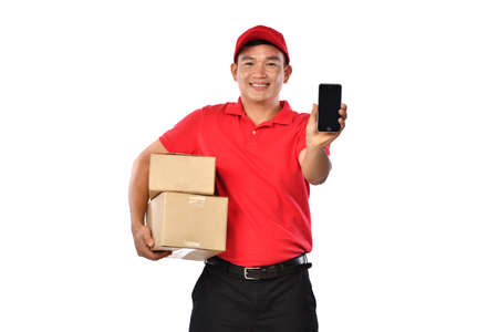 Asian delivery man in red uniform with parcel cardboard box showing mobile phone isolated on white background