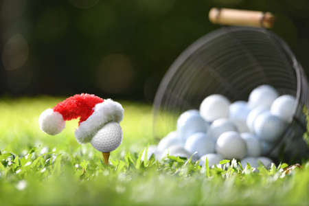Festive-looking golf ball on tee with Santa Claus' hat on top for holiday season on golf course background Banque d'images - 157822932