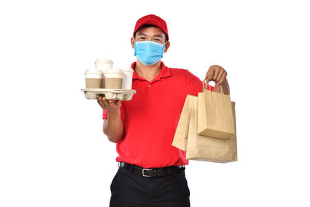 Happy young Asian delivery man in red uniform, medical face mask carry bags of food and drink in hands isolated on white background Banque d'images