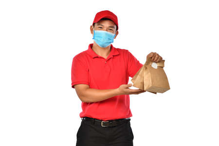 Happy young Asian delivery man in red uniform, medical face mask carry bags of food and drink in hands isolated on white background Banque d'images - 157937758