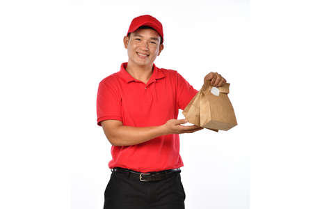 Asian delivery man in red uniform carry bags of food and drink in hands isolated on white background Banque d'images