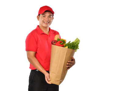 Asian delivery man in red uniform carry grocery bag in hands isolated on white background Banque d'images
