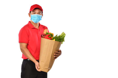Happy young Asian delivery man in red uniform, medical face mask carry grocery bag in hands isolated on white background Banque d'images
