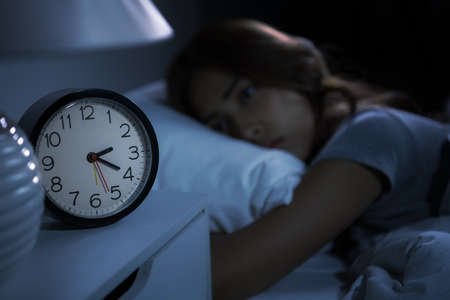 Depressed young woman lying in bed cannot sleep from insomnia. Selective focus on alarm clock