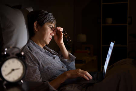 Asian senior woman having sore and tired eyes when using a laptop in her bed at night