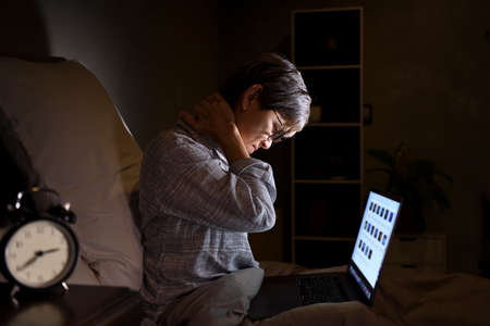 Senior Asian woman with sore and muscle pain from laptop use in bed Standard-Bild