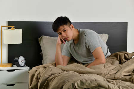 Depressed young Asian man sitting in bed cannot sleep from insomnia Фото со стока