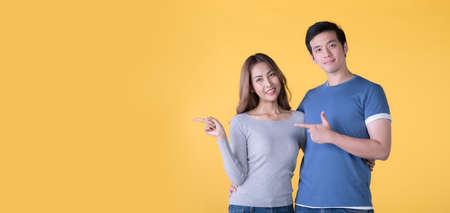 Happy Asian couple pointing fingers at empty copy space for text over yellow background
