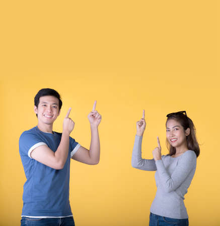 Happy Asian couple pointing fingers up at empty copy space for text over yellow background Фото со стока