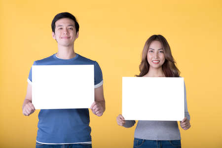 Asian couple holding empty blank boards and smiling at camera isolated on yellow background