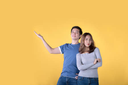 Happy Asian couple showing and presenting copy space in business and looking at the camera over yellow background