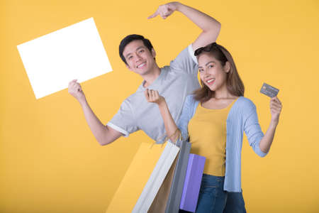 Asian couple holding blank billboard with credit card and shopping bags isolated on yellow background