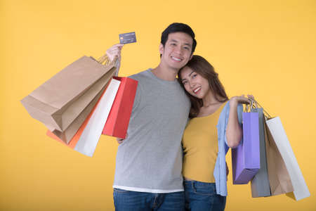 Asian couple holding credit card and shopping bags isolated on yellow background Фото со стока