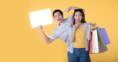 Asian couple holding blank billboard and shopping bags isolated on yellow background