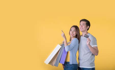 Asian couple holding credit card and shopping bags pointing and looking up isolated on yellow background