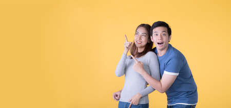 Excited Asian couple pointing fingers at empty copy space for text over yellow background
