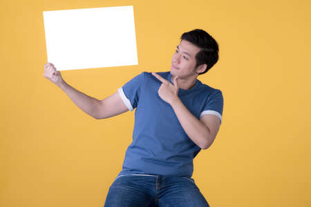 Asian man in casual clothes holding empty blank board and pointing finger isolated on yellow background