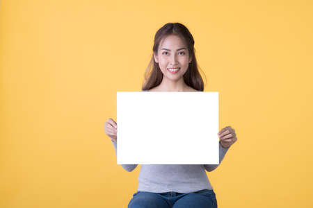 Asian woman in casual clothes holding empty blank board isolated on yellow background Фото со стока