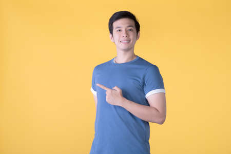 Asian man in casual clothes pointing fingers at empty copy space for text over yellow background Фото со стока