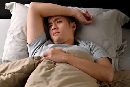 Depressed young Asian man lying in bed cannot sleep from insomnia
