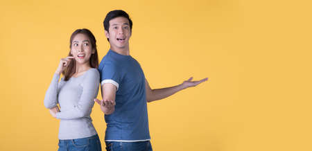 Excited Asian couple in casual clothes presenting with hands open to copy space isolated on yellow background Фото со стока