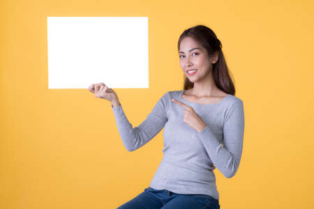 Asian woman in casual clothes holding empty blank board and pointing finger isolated on yellow background