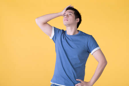 Asian man is bored, isolated on yellow background