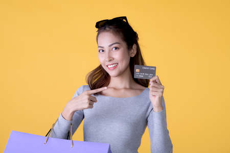 Happy Asian woman carry shopping bags and pointing at credit card smiling over yellow background, empty space