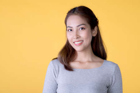 Portrait of a beautiful smiling young Asian woman in casual clothes standing isolated over yellow background, looking at camera Фото со стока
