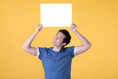 Asian man holding empty blank board isolated on yellow background