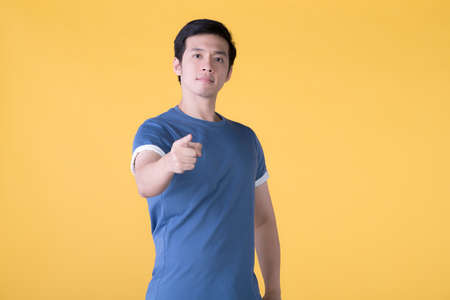 Young Asian man in casual clothes points finger to you and the camera with a confident expression isolated on yellow background Фото со стока