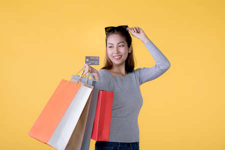 Happy Asian woman with shopping bags and credit card smiling over yellow background, empty space Фото со стока
