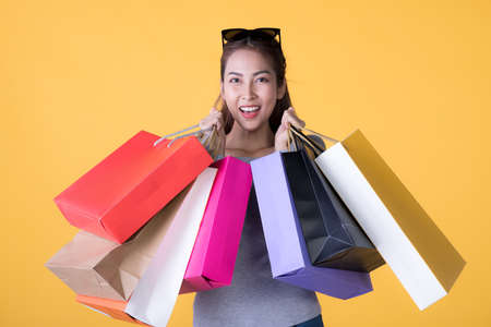 Portrait of a cheerful Asian woman holding shopping bags looking and smiling at camera isolated over yellow background