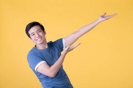 Happy Asian man pointing fingers up at empty copy space for text over yellow background Фото со стока