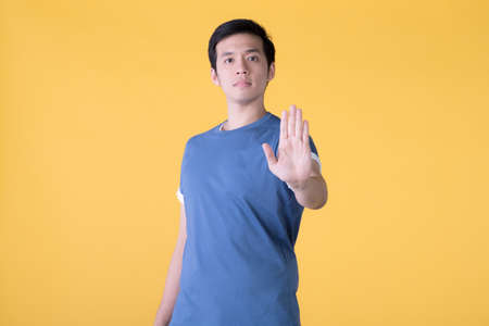 Young Asian man wearing casual clothes over yellow background doing stop sing with palm of the hand