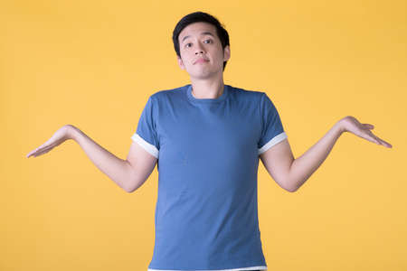 Asian man in casual clothes presenting with hands open to copy space isolated on yellow background