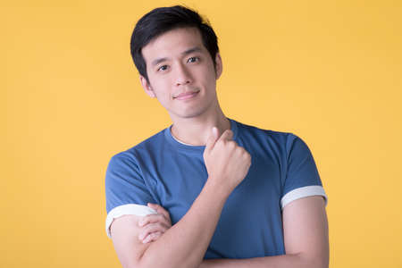 Close up portrait of smiling handsome Asian young man isolated on yellow background Фото со стока