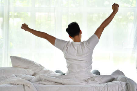 Asian man waking up in the morning sitting on bed and stretching Фото со стока
