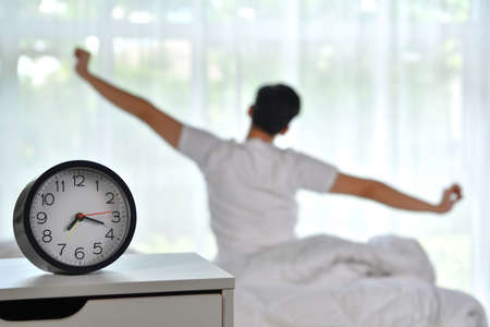 Man waking up in the morning sitting on bed and stretching, focus on alarm clock