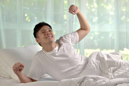Asian man stretching in bed after wake up in the morning