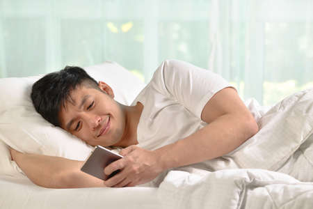 Young Asian man using smartphone in bed after waking up in the morning