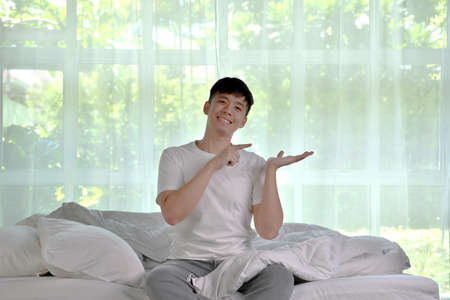 Asian man waking up in the morning sitting on bed and showing empty copy space on the open hand palm for text Фото со стока