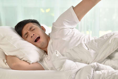 Young asian man yawning and stretching while waking up in the morning