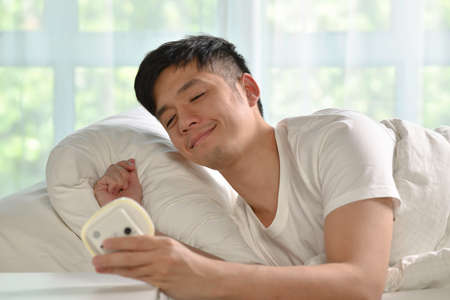 Portrait of happy Asian man waking up in bed in the morning Фото со стока