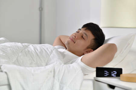 Handsome Young Asian man sleeping in bed Фото со стока