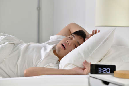Young Asian man sleeping and snoring loudly lying in the bed