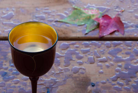 Golden cup and autumn leaves against a wooden background photo